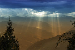 Sun shine from Cloud burst - Sikkim , India. Sun rays coming out of cloud burst - at Rabangla, Sikkim, India. Trees in foreground and Himalayan mountains in Royalty Free Stock Photo