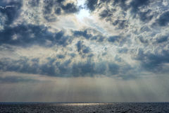 The sun shines behind the clouds Stock Image