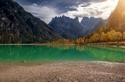 The sun shines through big majestic mountains view of the dolomites Cristallo group Lake Landro. The sun shines through big majestic mountains view of the Stock Photography