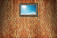 sun shines on blue sky with clouds in wooden frame on brick wall Stock Image