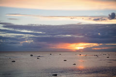 The sun shines through a cloud over the sea. In the sunset hour Royalty Free Stock Photography