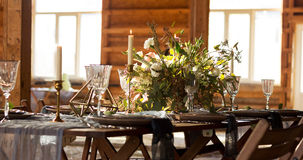 The sun shines Decoration wedding table.  Big windows. Wedding p. The sun shines Decoration wedding table before a banquet in a wooden barn. Big windows. Wedding Royalty Free Stock Photo