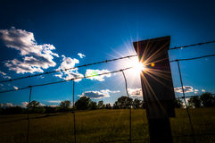 The sun shines through a fence Stock Photos