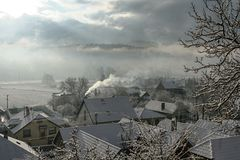 Sun shines through heavy clouds on town Slovenska Lupca covered with snow. During winter season before Christmas. Smoking chimney, tree branches and snow royalty free stock image