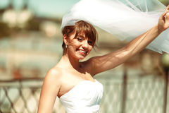 Sun shines over a beautiful bride posing on the roof royalty free stock image