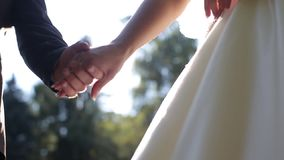 Sun shines over bride and groom holding each other hands together stock video footage