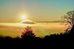 Sun shines over a sea of clouds stock photos