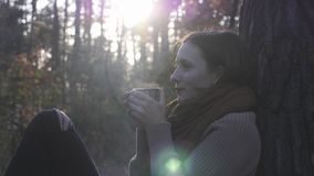 Sun shines over stunning woman in cozy sweater, jeans and boots drinking hot drink in autumn forest. Portrait of young handsome fe. Male in fall forest stock footage