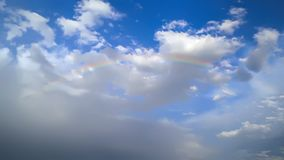 Bright rainbow on a background of white cumulus clouds royalty free stock image