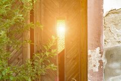 The sun shines through the window in the old door stock images