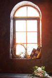Sun is shining in a beautiful window on which there are old books and lay a bouquet of flowers of roses. Bright evening sunlight Royalty Free Stock Image