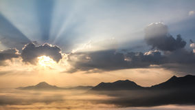 Sun shining behind the clouds on the mountain Stock Image