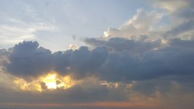 The Sun shining behind the huge, thick dark cloud. Royalty Free Stock Image