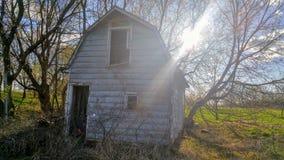 Sun shining behind old Barn Stock Image