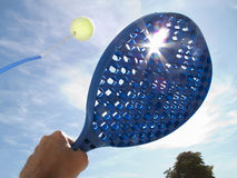 Sun shining behind paddle hitting tennis ball Stock Photo