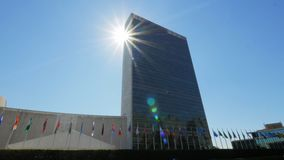 Sun shining behind united nations building stock footage
