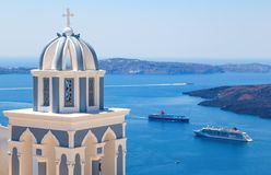 Sun shining through belltower of church with a view of Santorini volcanic caldera and ships in it, Santorini, Cyclades Royalty Free Stock Image