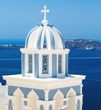 Sun shining through belltower of church with a view of Santorini volcanic caldera and ships in it, Santorini, Cyclades Royalty Free Stock Photography