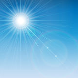 Sun is shining brightly with a flare on a blue sky background. Royalty Free Stock Images