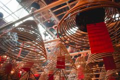 Sun shining through buddhist spiral burning sticks in a temple in Hong Kong China royalty free stock image