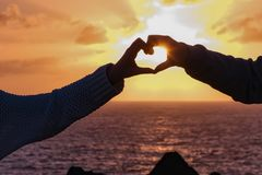 Sun is shining through children s hand forming a heart, sunset in Lanzarote. Two girls are forming together with their hands a heart  and the sun during sunset royalty free stock photo