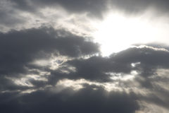 Sun shining clouds. The sun is shining brightly from behind several clouds in the sky Royalty Free Stock Photos