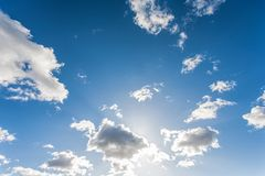 Sun shining through clouds on a clear blue sky. The sun shining through clouds on a clear autumn morning Stock Photos