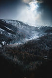 Sun shining through clouds over high snowy mountains Royalty Free Stock Photos