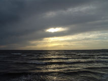 Sun shining through clouds over ocean at sunset karachi pakistan Stock Photo