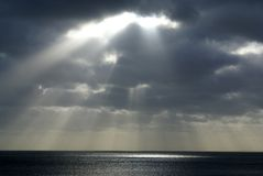 Sun shining through clouds over the south coast Stock Photo