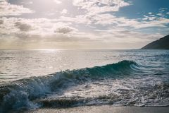 Sun shining through the clouds at sandy beach with waves royalty free stock images