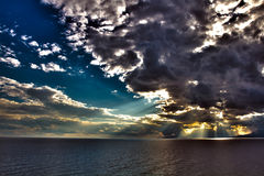 Sun is shining through the clouds. On the sea before the storm. HDR snapshot royalty free stock image