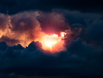 Dramatic Sky. The powerful sun is breaking through a hole in the dark and ominous sky. Opportunity or breakthrough concept. Light at the end of the tunnel royalty free stock images