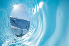 Sun shining into the entrance of a large round ice cave in the Matanuska Glacier in Alaska. Deep in the Alaskan wilderness, far back on the Matanuska Glacier stock photo