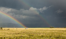 Sun shining on grassland under storym and rain royalty free stock photography