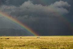 Sun shining on grassland under storym and rain stock image