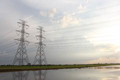 The sun is shining.Hight power transmission tower are located on a green field. Many wires are tied a cross The water to see the full field royalty free stock images