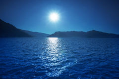 Sun shining over blue water of fresh water lake and mountain bac Stock Photos
