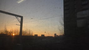 Sun shining over city in the morning. Early morning cityscape view through moving train dirty window stock footage