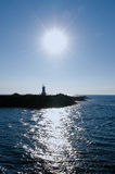 Sun shining over lighthouse Stock Photo