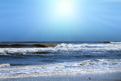 Sun shining over ocean shore Stock Images