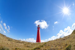 Sun shining over red lighthouse Royalty Free Stock Photography