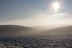 Sun shining over snowy field. Scenic view of sun shining over snow covered field in countryside with hills in background stock photo