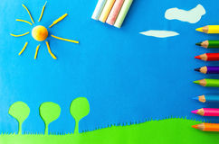 Children`s play :sunny days. Sun shining over the trees on blue background Royalty Free Stock Images