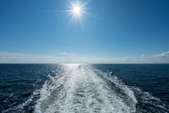Sun shining over the wake of cruise ship at sea Stock Images