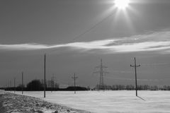 Sun shining over wintry landscape. Black and white scenic view of sun shining over snowy countryside landscape with telegraph poles Stock Image