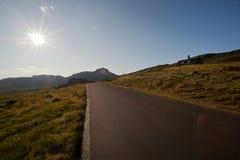 Sun shining on the road through mountain plateau Valdresflye Stock Photos