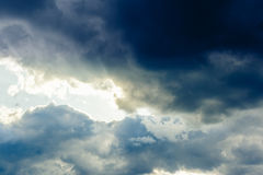 Sun shining through the stormy clouds. God rays, sky background stock image