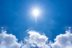 The sun is shining in th blue sky and cloud at noon time stock photo
