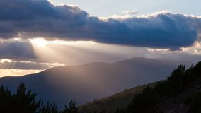 Sun shining through thick clouds over mountains right before sunset. royalty free stock photo